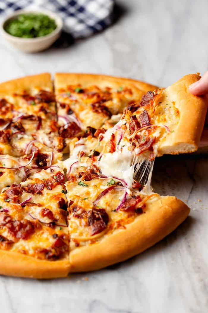 Hand pulling a slice of chicken bacon ranch pizza up, with cheese pulling at the edges