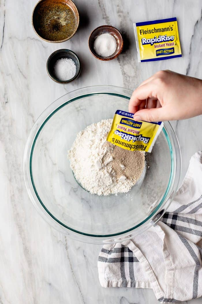 Hand pouring a package of yeast into a bowl of flour on a marble surface
