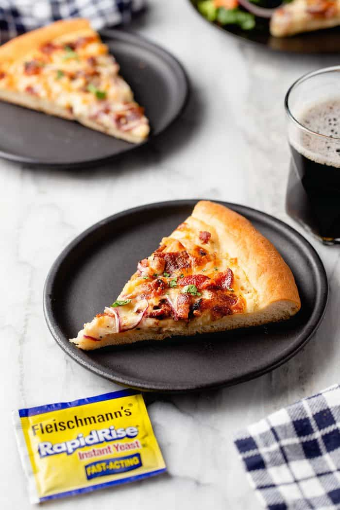 Slices of chicken bacon ranch pizza on black plates next to a glass of soda