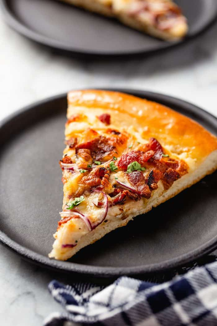 Slice of chicken bacon ranch pizza on a black plate