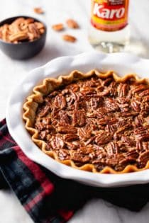 Baked chocolate pecan pie in a white pie plate on top of a plaid towel