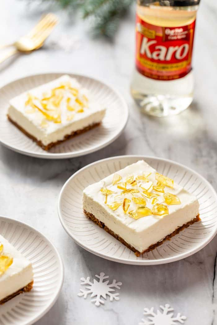 Two white plates with slices of no-bake cheesecake bars topped with cracked sugar. A bottle of corn syrup is in the background