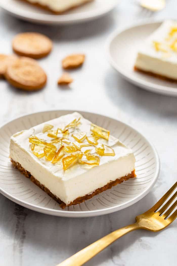 No-bake cheesecake bar with cracked sugar topping on a white plate next to a gold fork