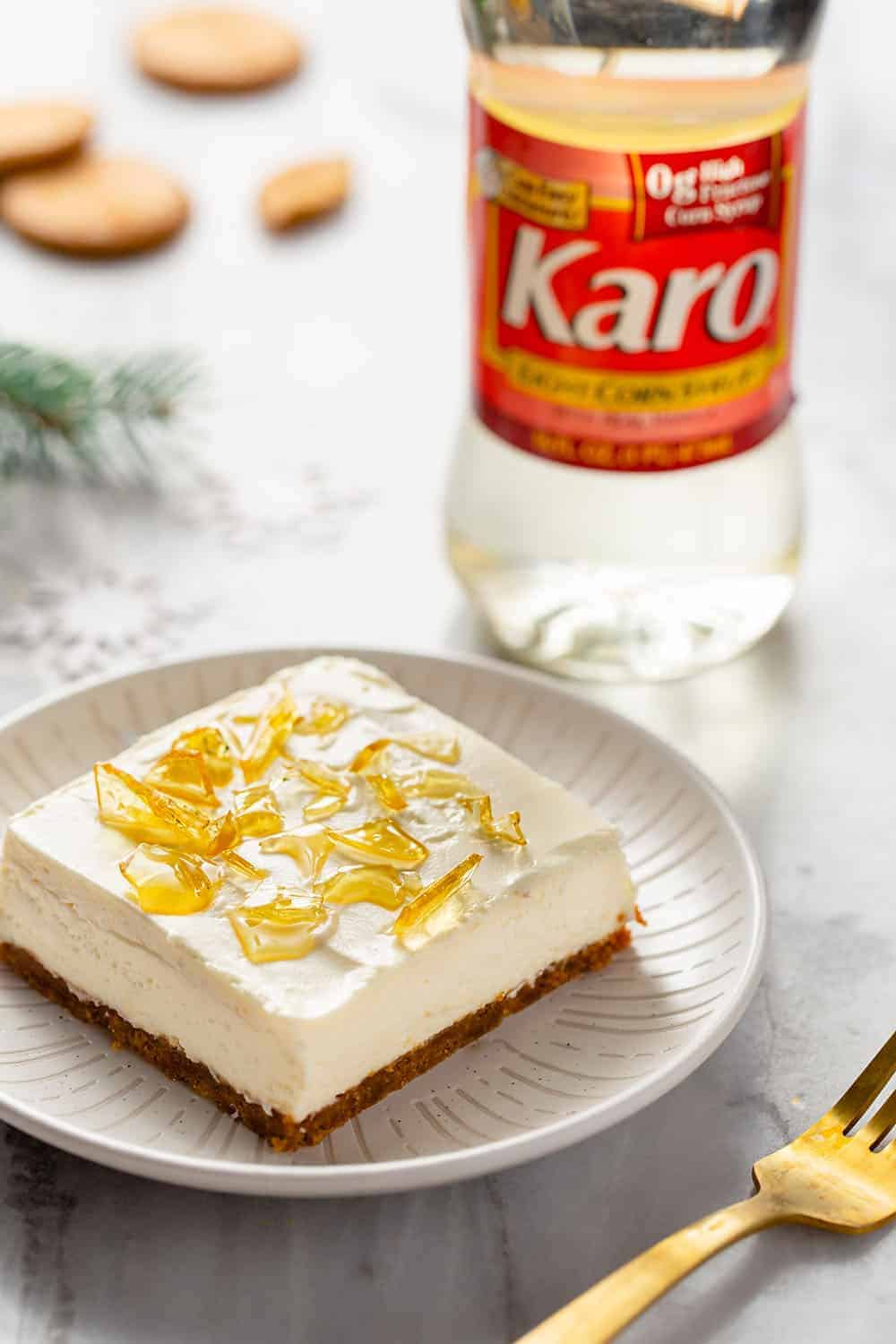 No-bake cheesecake bar with cracked sugar topping on a white plate with a bottle of corn syrup in the background