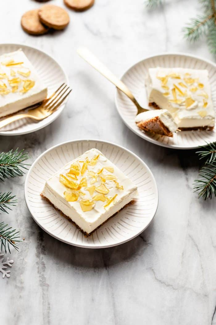 Three white plates each with a slice of no-bake cheesecake bar with sugar topping