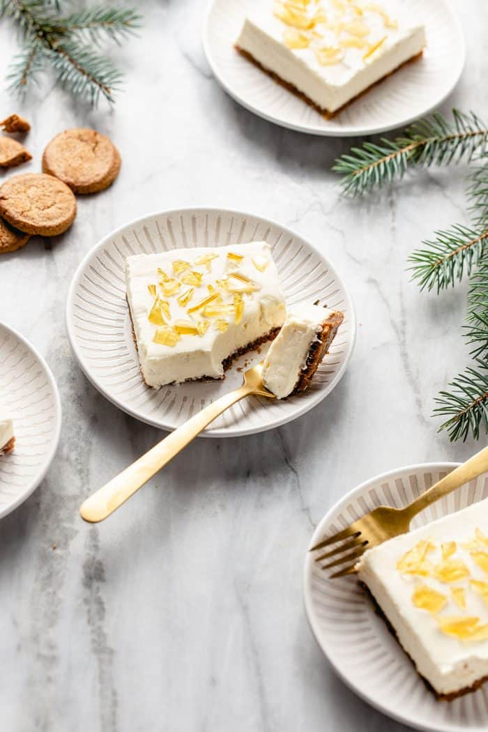 White plates holding slices of no-bake cheesecake bars arranged on a marble counter among sprigs of greenery