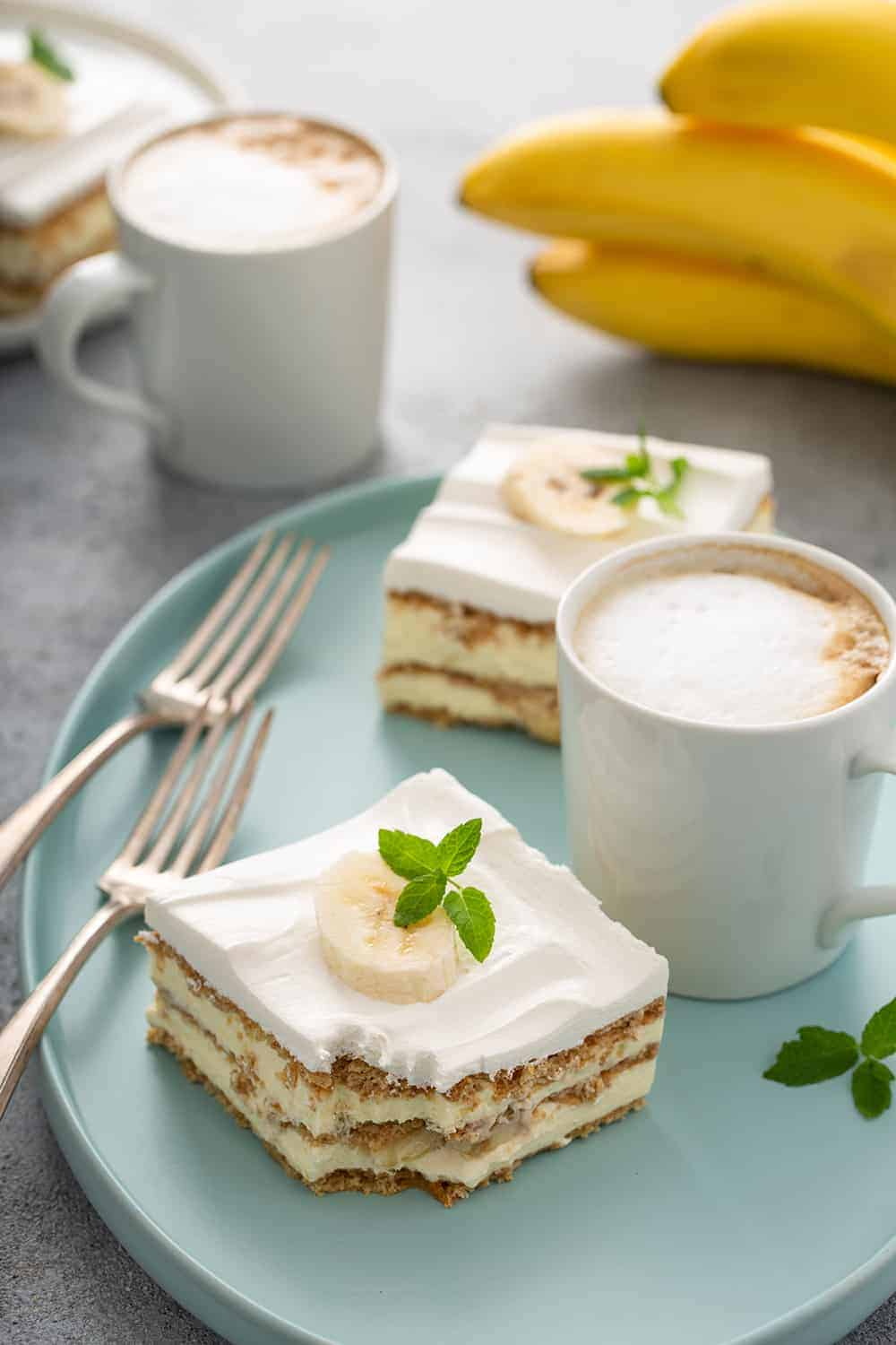 Two slices of banana eclair cake next to a latte and two forks on a blue platter, with another latte and a bunch of bananas in the background