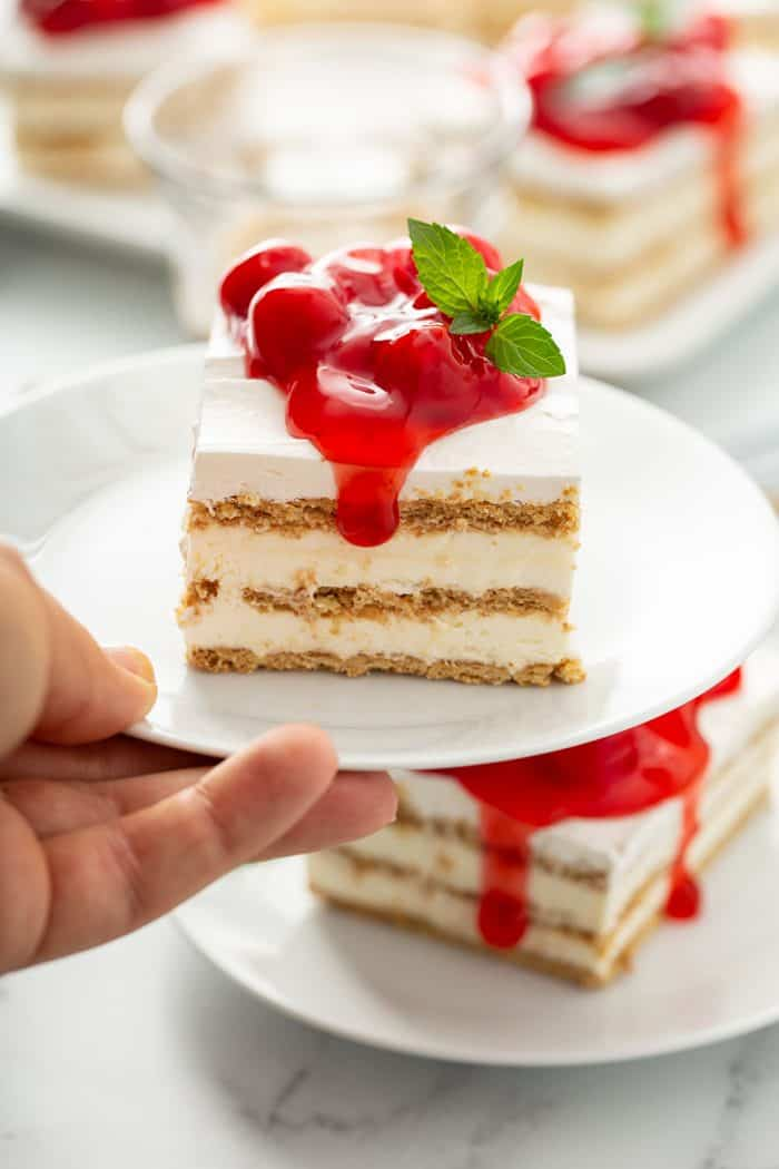 Hand holding up a plate with a slice of no-bake cheesecake eclair cake, showing layers of graham crackers and filling