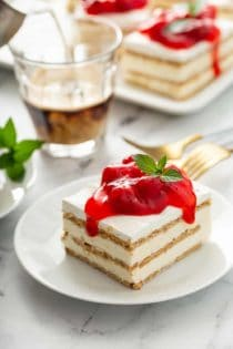 Slice of no-bake cheesecake eclair cake topped with cherry pie filling on a white plate, with a cup of espresso and more slices of eclair cake in the background