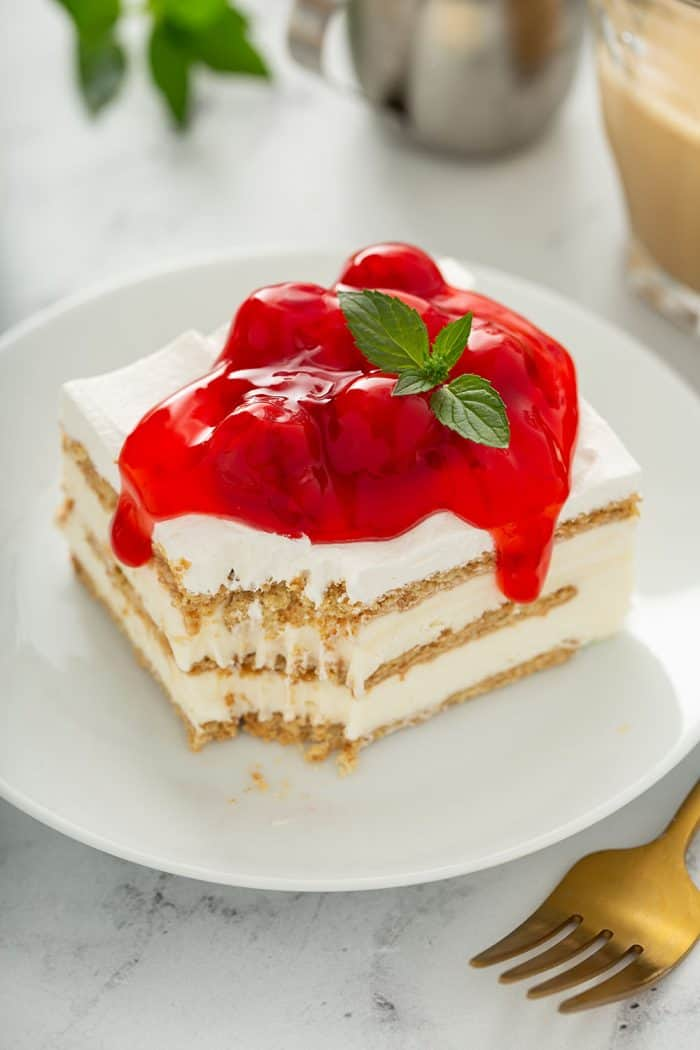 Slice of cheesecake eclair cake on a white plate, with a bite taken out of one corner