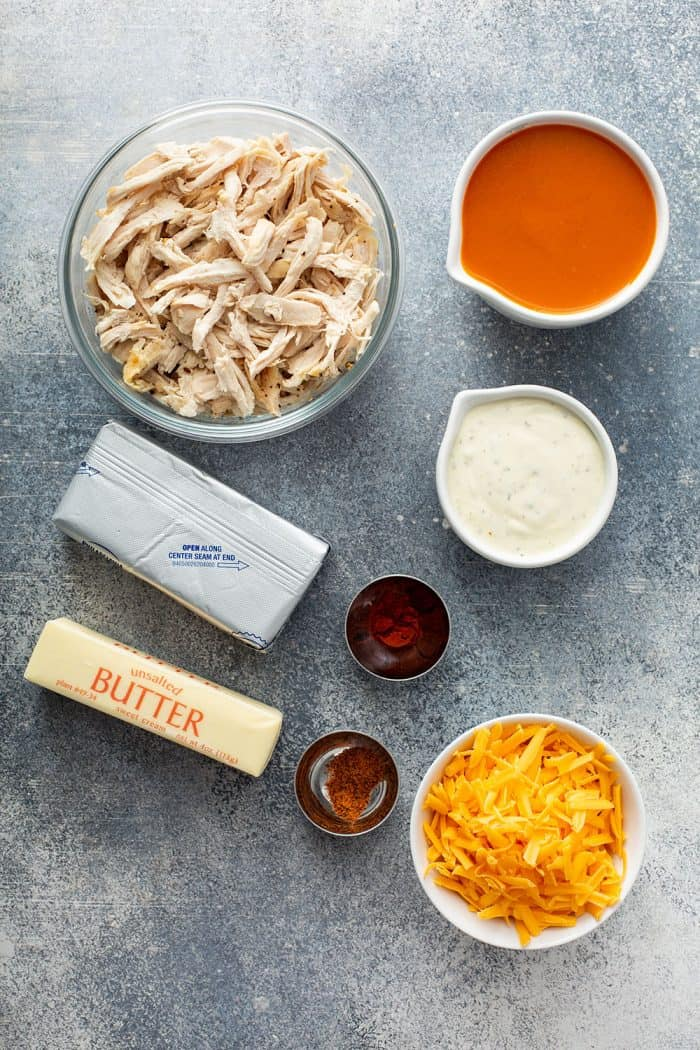 Overhead view of the ingredients for buffalo chicken dip arranged on a concrete counter