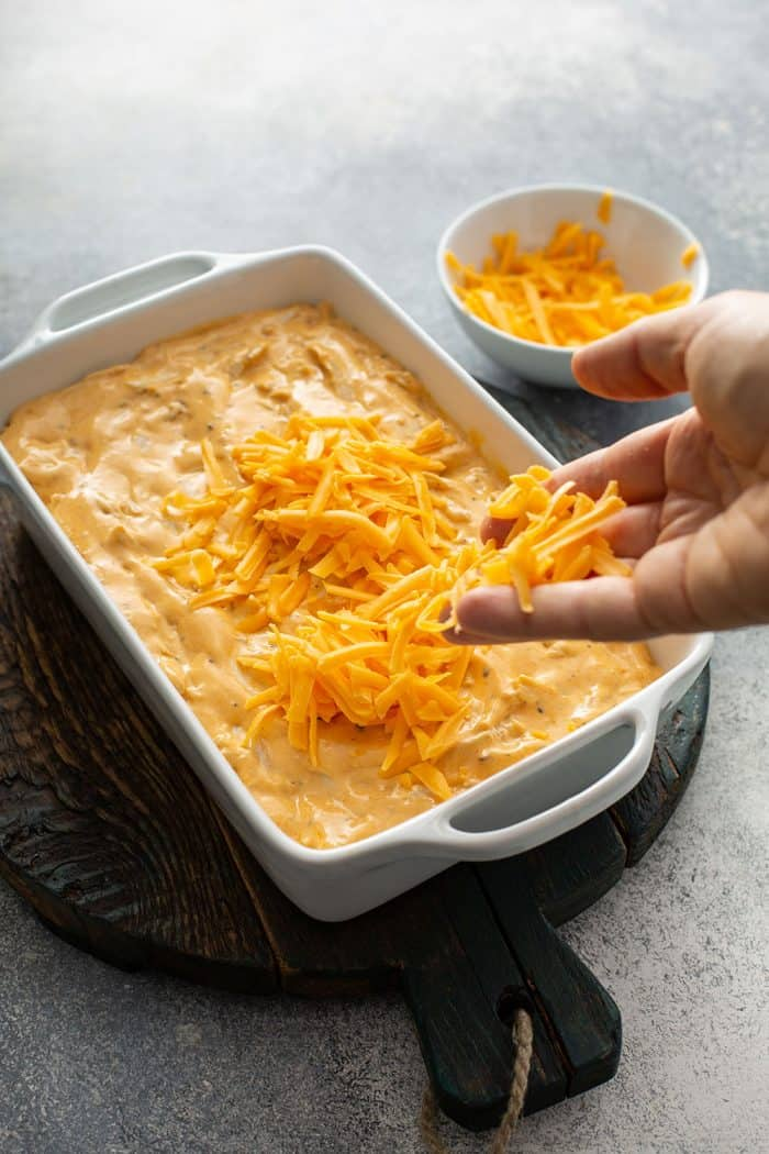 Hand sprinkling cheddar cheese on top of buffalo chicken dip in a white casserole dish