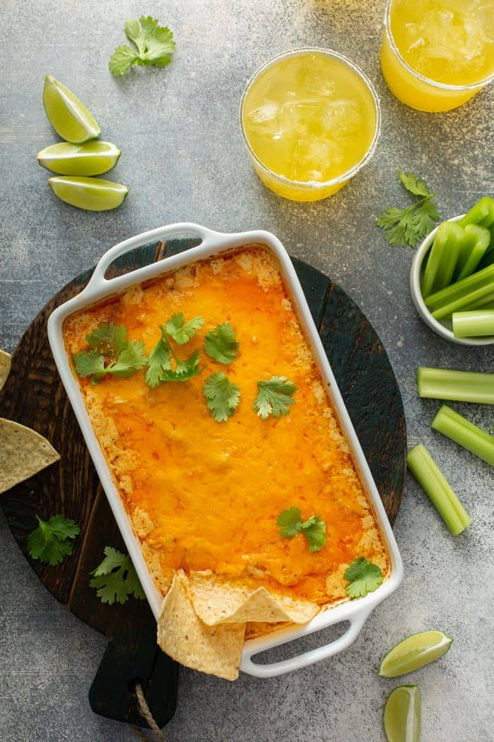 Overhead view of baked buffalo chicken dip in a white casserole dish surrounded by celery sticks and margaritas
