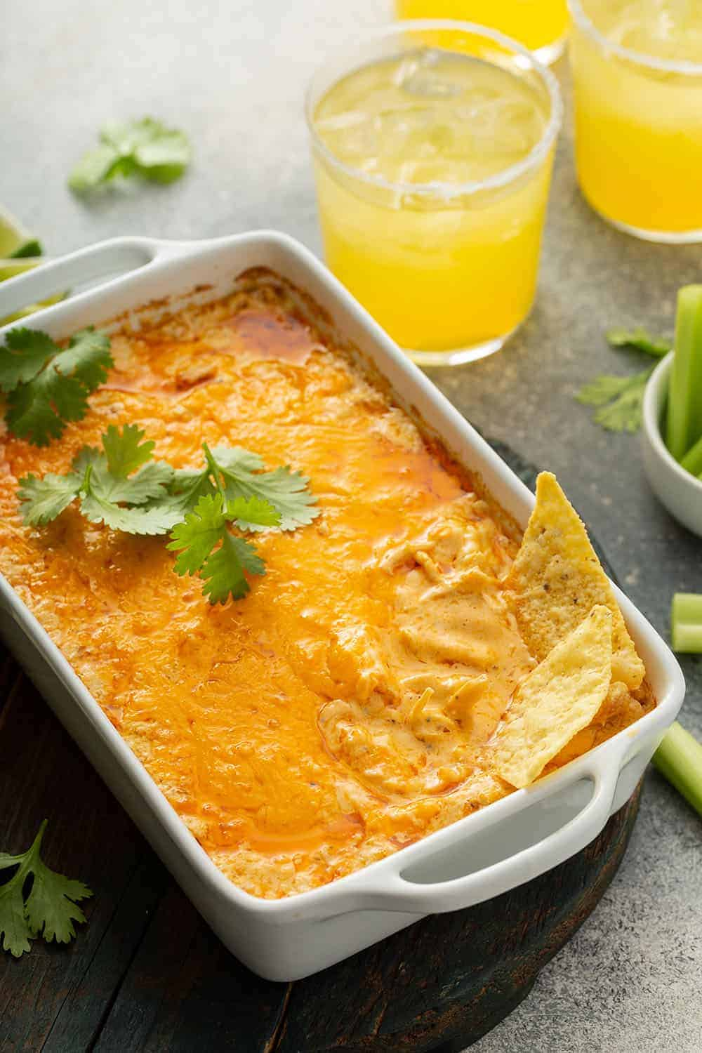 Tortillas sticking out of a buffalo chicken dip in a white casserole dish, with margaritas in the background