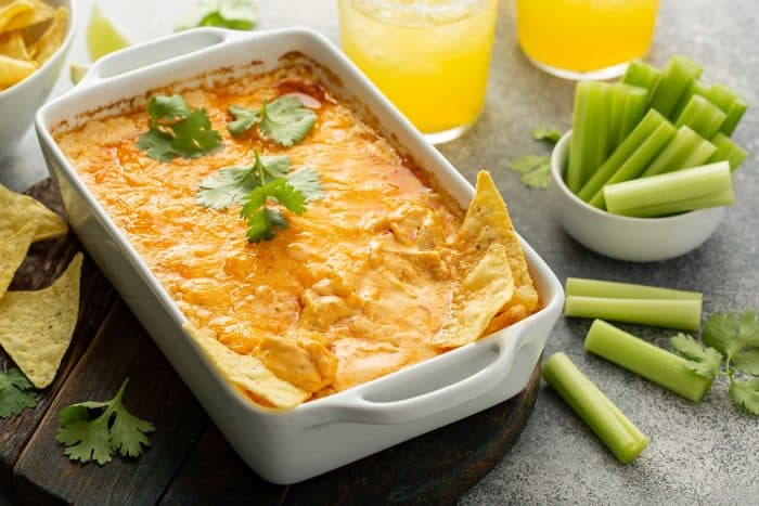 White casserole dish with buffalo chicken dip next to celery sticks on a concrete counter