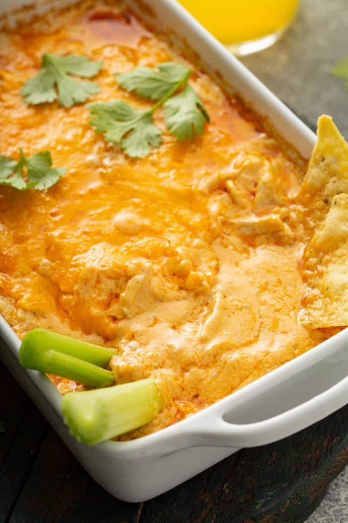 Celery sticks and tortilla chips sticking out of buffalo chicken dip in a white casserole dish
