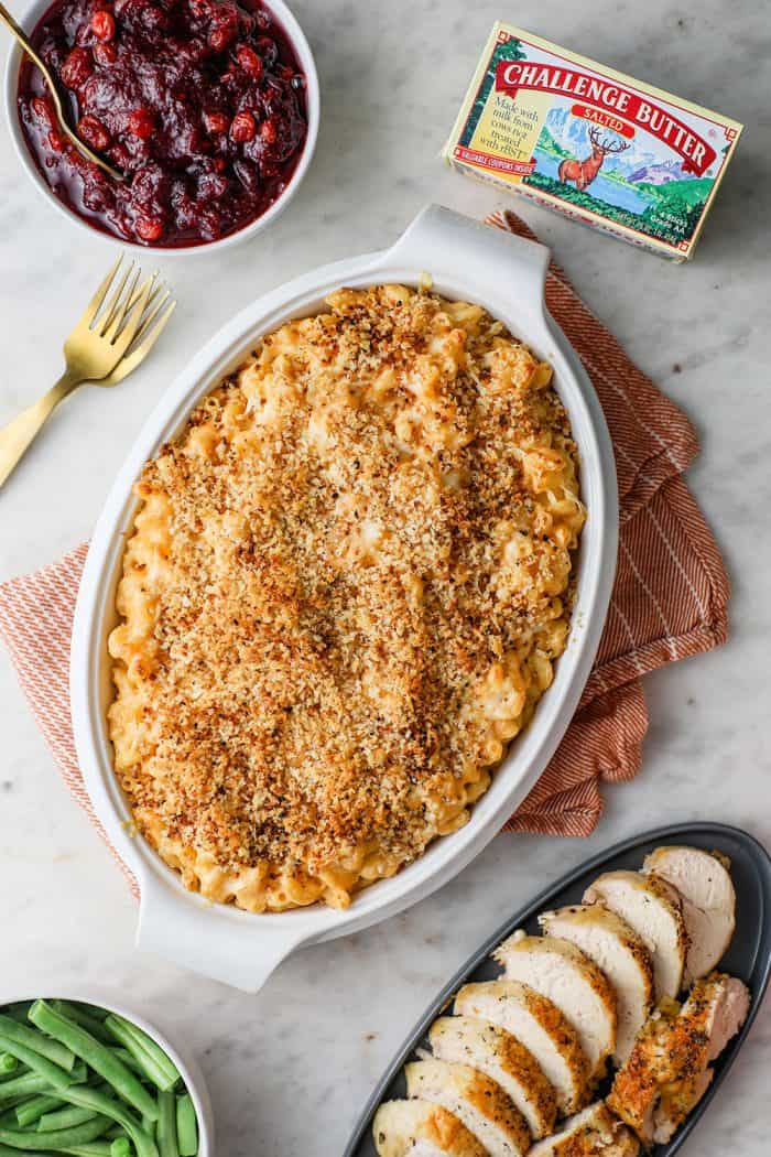 Casserole dish of baked macaroni and cheese on a table next to other Thanksgiving sides