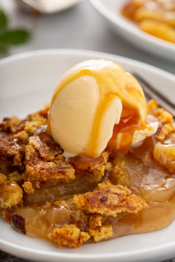 Close up of plated apple dump cake topped with vanilla ice cream and caramel sauce
