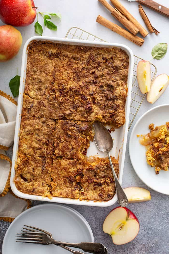 Spoon about to scoop a slice of apple dump cake out of the pan