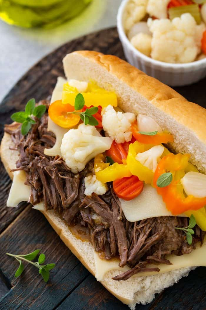 Close up of italian beef on a hoagie roll topped with giardiniera