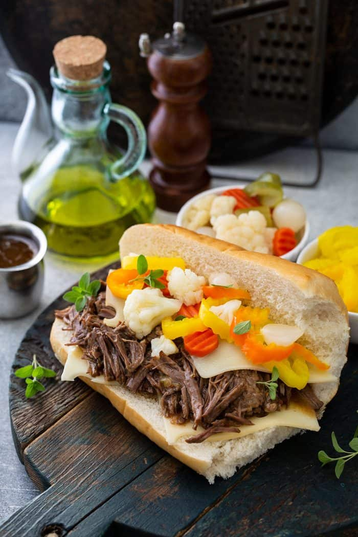 Assembled italian beef sandwich topped with giardiniera