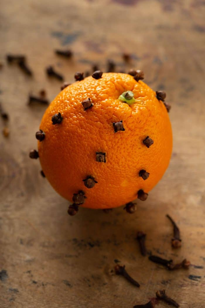 Orange studded with cloves on a countertop