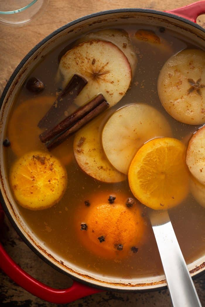 Mulled wassail in a red dutch oven with a ladle in it