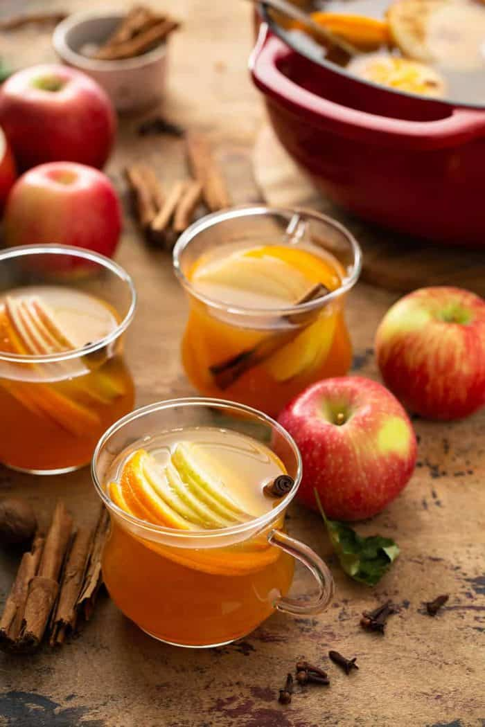 Three mugs of hot wassail garnished with sliced apples and cinnamon sticks with a dutch oven full of wassail in the background