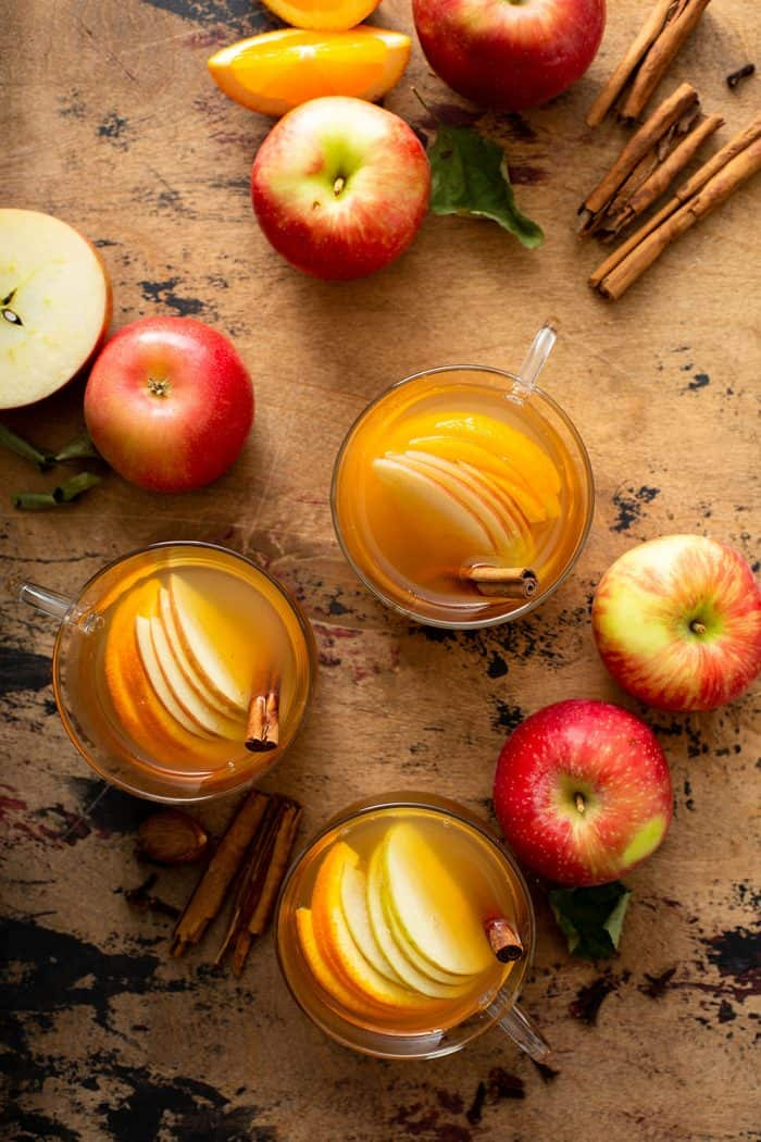 Overhead view of three mugs of wassail surrounded by apples and cinnamon sticks