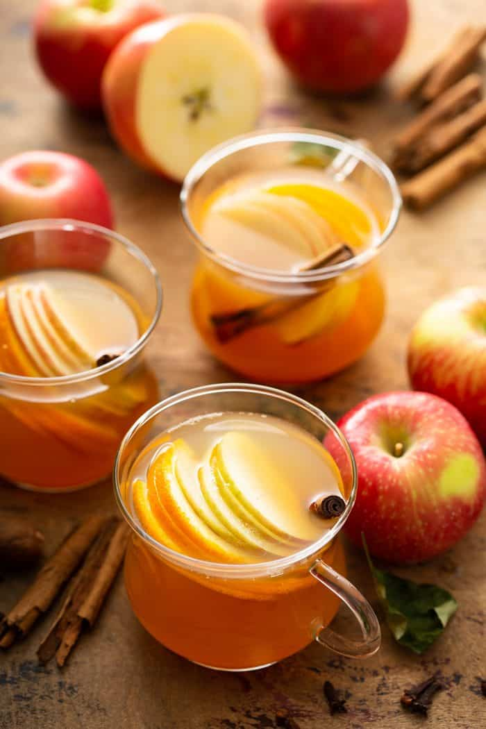 Three mugs of wassail garnished with sliced apples and cinnamon sticks, surrounded by more whole apples