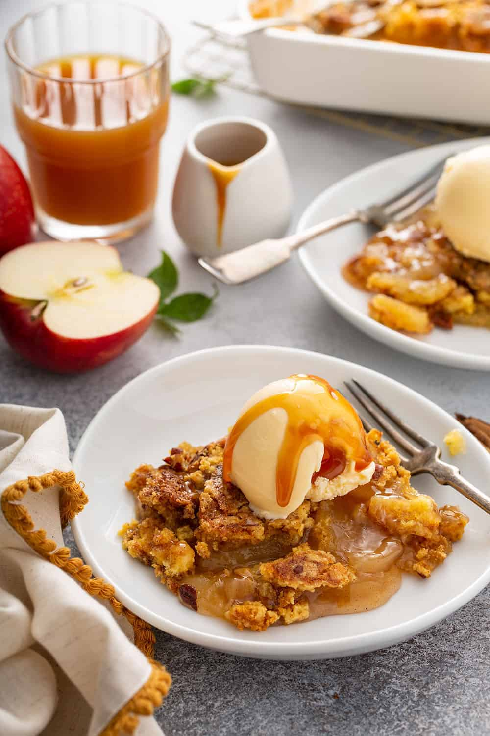 Two shallow bowls filled with apple dump cake topped with vanilla ice cream and caramel sauce