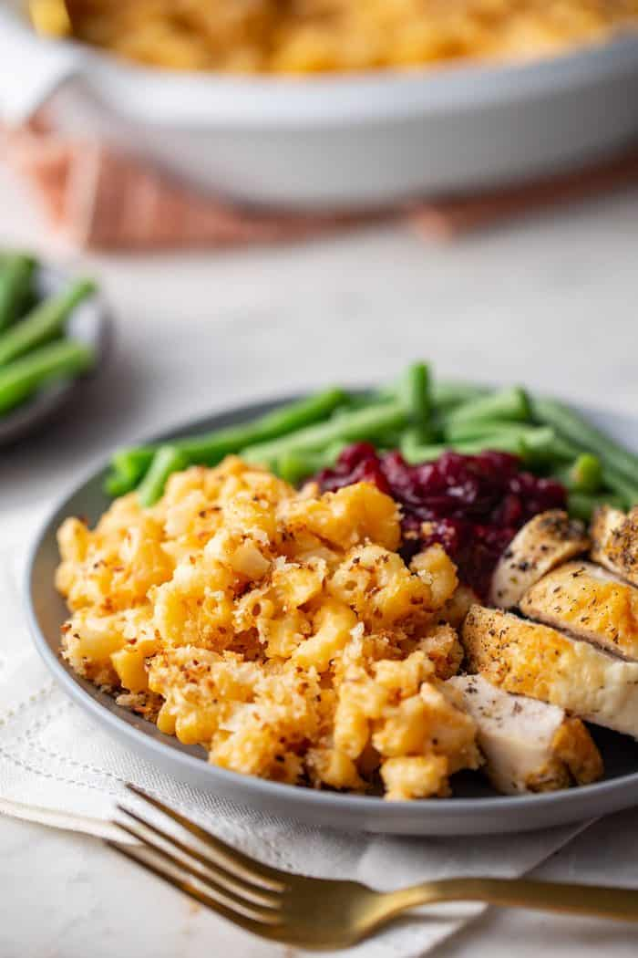 Close up of baked macaroni and cheese on a plate with other Thanksgiving sides