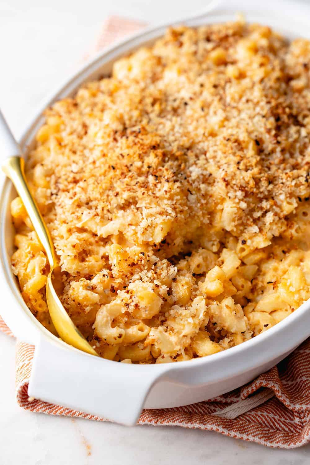 Spoon about to serve baked macaroni and cheese out of a white casserole dish