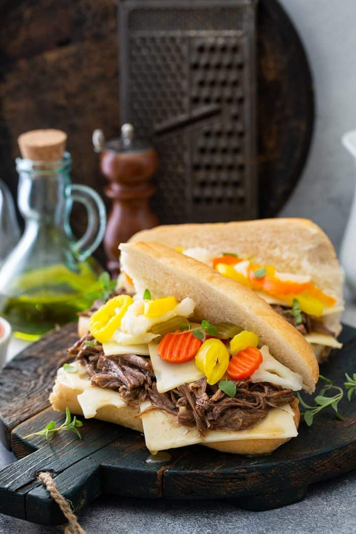 Two assembled Italian beef sandwiches on a wooden board