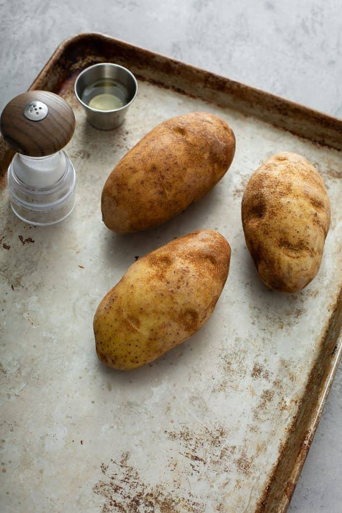 Three baking potatoes, salt and pepper on a sheet tray