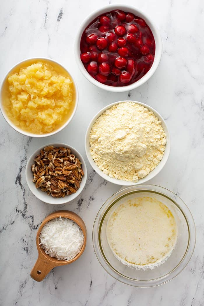 Ingredients for cherry pineapple dump cake on a marble countertop