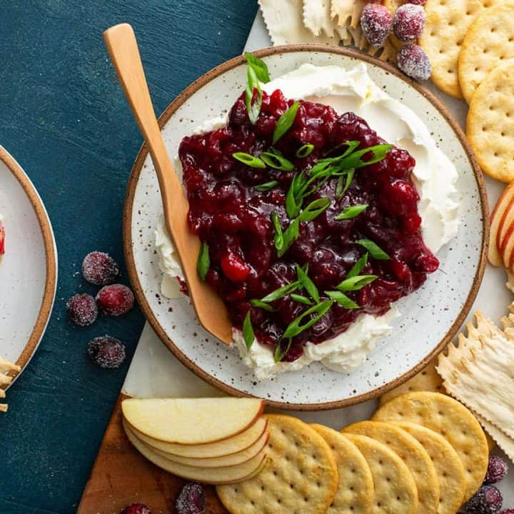 Cranberry cream cheese dip on a platter next to crackers and sliced apples