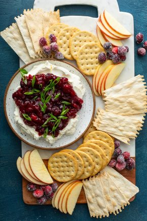 Plate of cranberry cream cheese dip surrounded by crackers