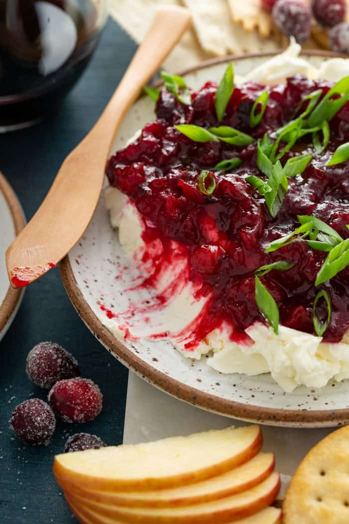Wooden butter knife on the edge of a plate of cranberry cream cheese dip