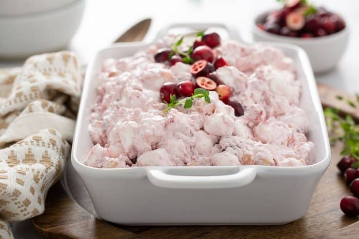 Cranberry fluff in a white serving dish, garnished with fresh cranberries