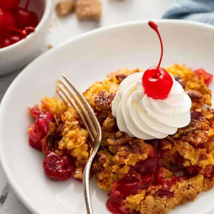 Fork about to take a bite of cherry pineapple dump cake topped with whipped cream and a cherry