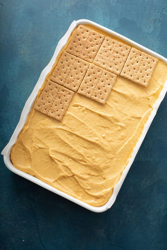 Graham crackers being layered on top of pumpkin filling in a cake pan