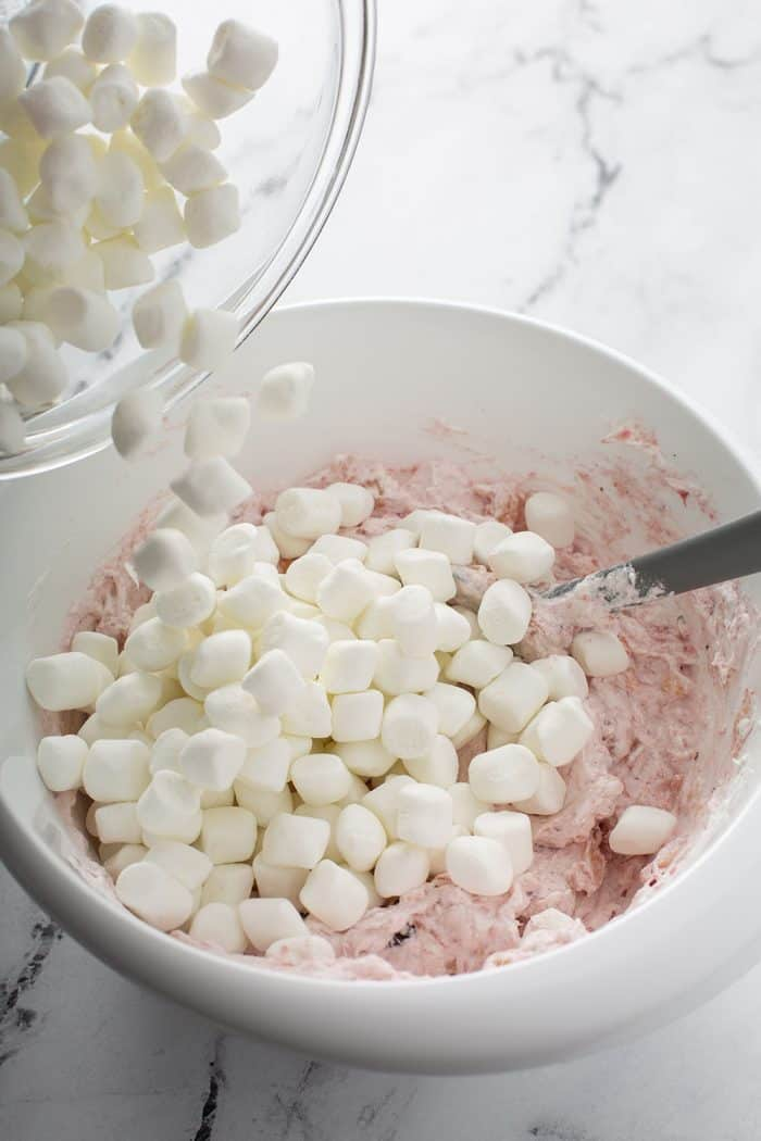 Mini marshmallows being added to a white mixing bowl