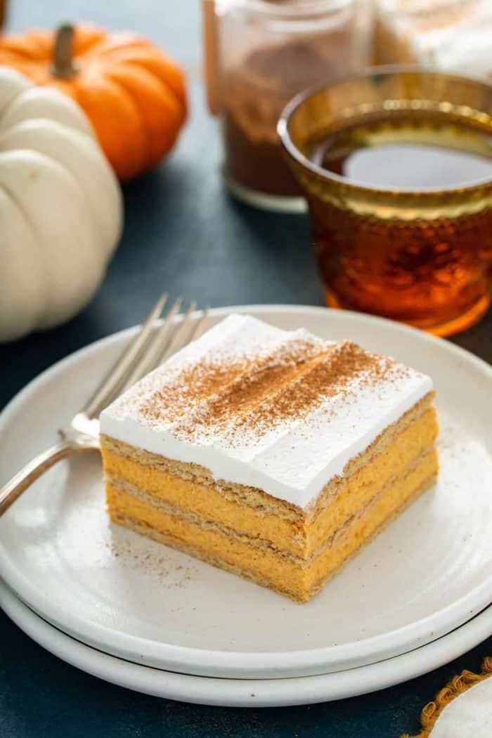Fatia de bolo de éclair de abóbora ao lado de um garfo em um prato branco