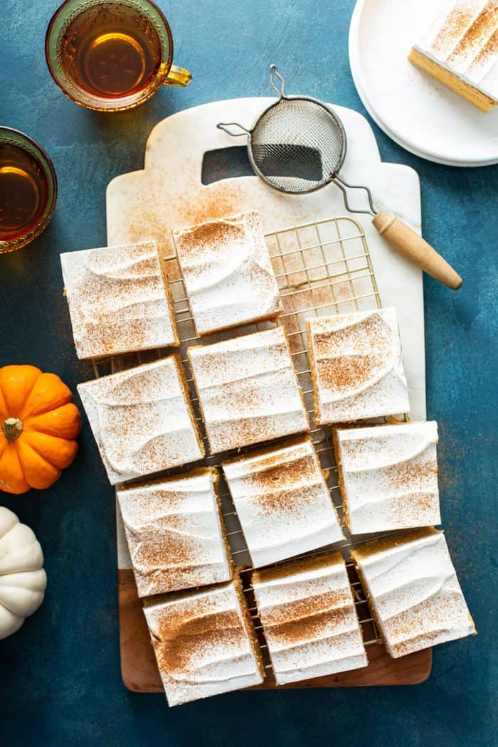 Eclair cake cut into pieces on a cutting board and dusted with cinnamon
