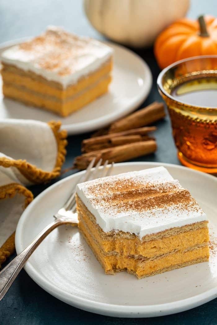 Fatia de bolo de eclair de abóbora com uma mordida retirada do canto em um prato branco.  Um segundo pedaço de bolo éclair está no fundo
