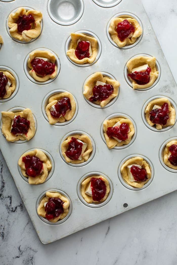 Unbaked cranberry brie bites in a mini muffin tin