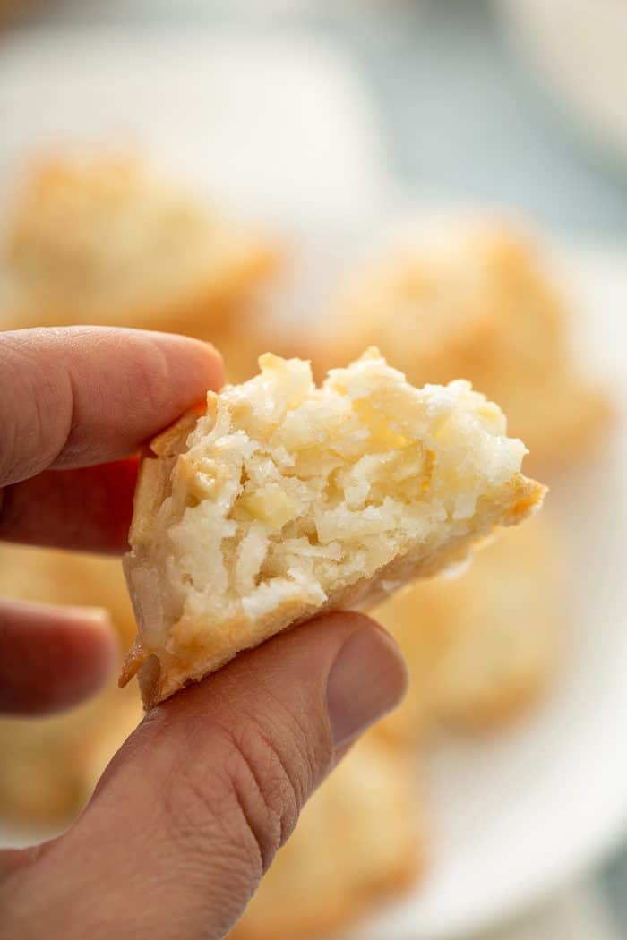 Hand holding up a coconut macaroon with a bite taken out of it