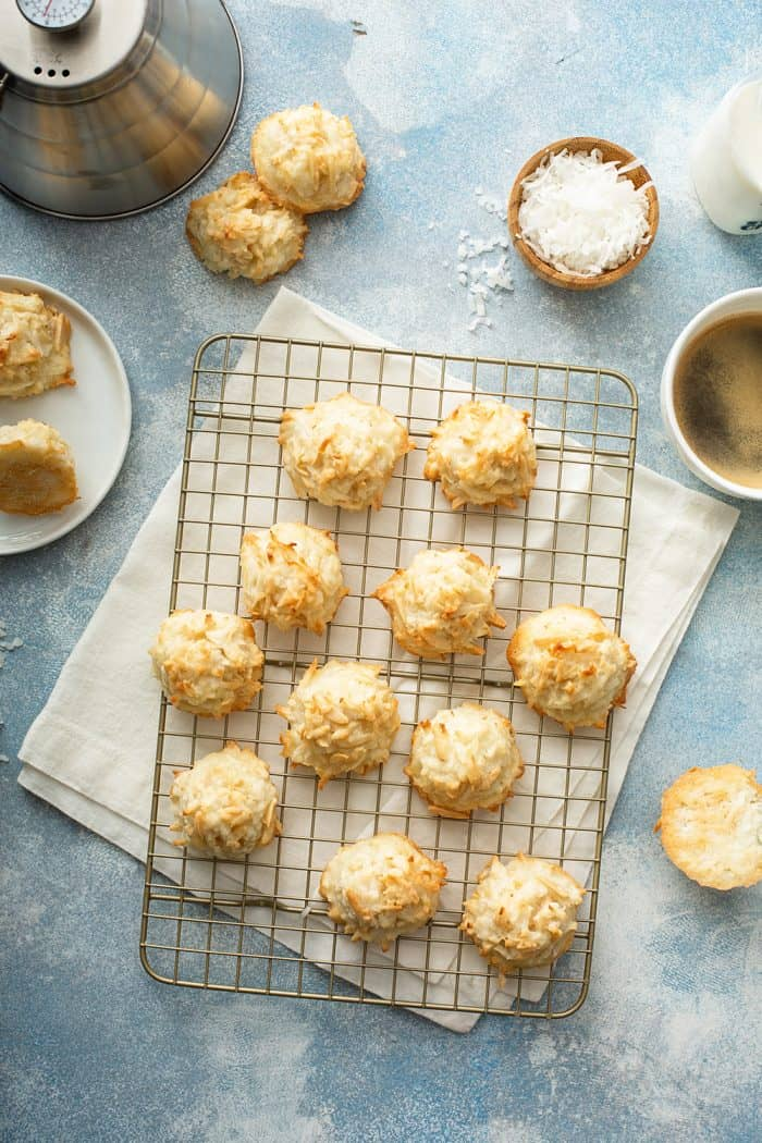 Coconut macaroons cooling on a wire rack surrounded by macaroon ingredients