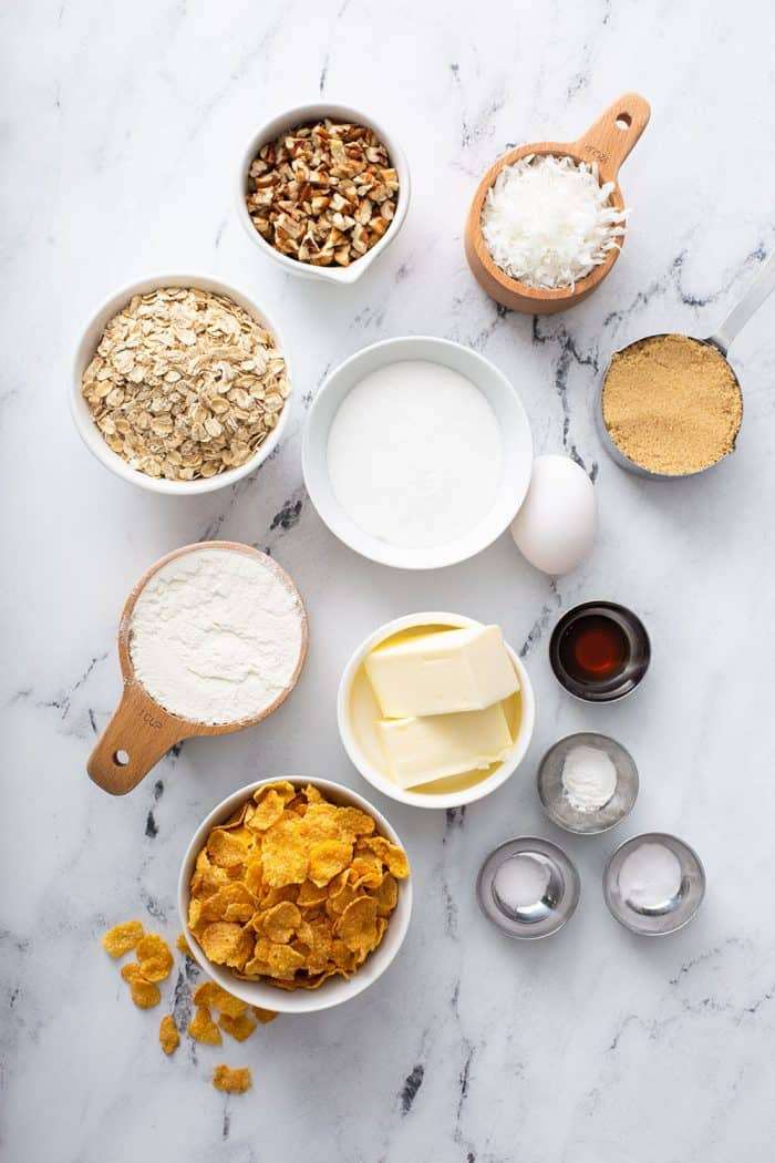 Ingredients for cornflake cookies arranged on a marble counter